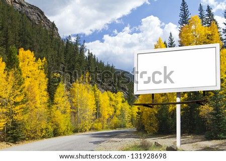 Mountain Road with Blank Billboard Sign and Fall Aspen Trees Forest - stock photo