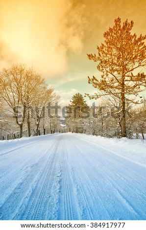 Mountain road with snow in winter at sunset