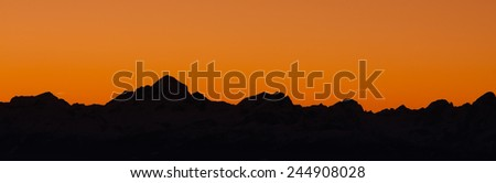 Mountain silhouette in the afterglow. View of Julian Alps in Slovenia with their highest peak Triglav, Slovenia  - stock photo