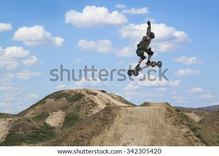 Mountain skateboarder jumping over the hill. Bright sky with clouds in the background - stock photo