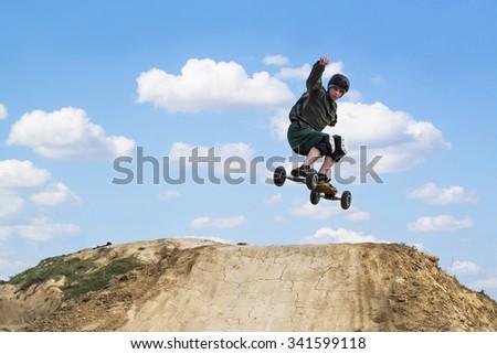 Mountain skateboarder jumping over the ramp in mountain skateboard park - stock photo