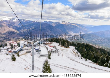 Mountain slopes with chairlift on a winter sunny day. Winter mountains panorama with ski slopes and ski lifts near ski center. - stock photo