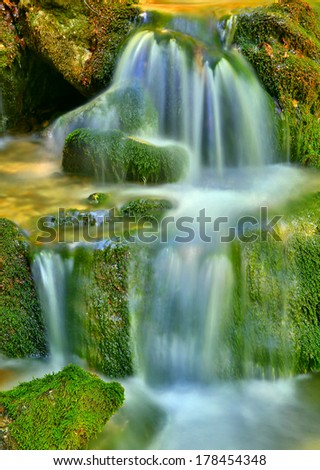 mountain stream among stones in green moss