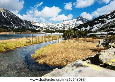 Mountain Stream and Grass Meadows surrounded by Snowy peaks - stock photo