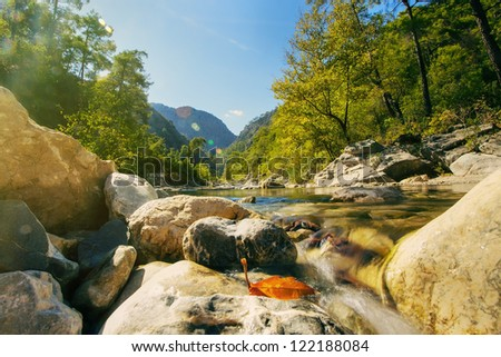 Mountain stream and sunrays - stock photo