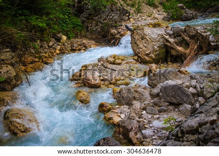 Mountain stream flowing between rocks - stock photo