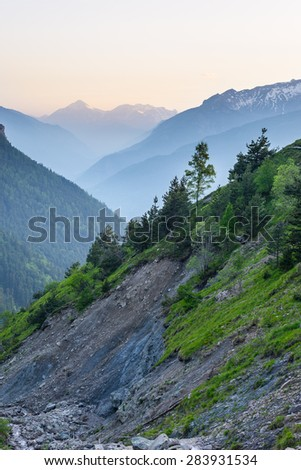 Mountain stream flowing in very steep valley with landslides and erosions on rocky slopes. Shot at dusk in the italian Alps with foggy valleys below and soft light. - stock photo