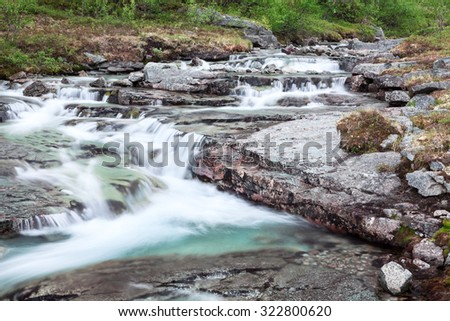 Mountain stream of melt water flowing from the peaks, long exposure - stock photo
