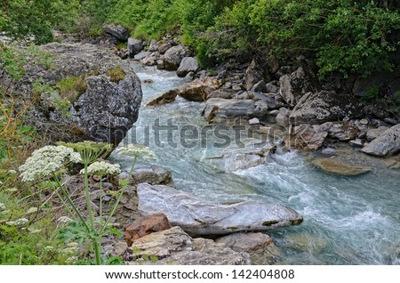 Mountain stream runs on the rocks with transparent cascades and white shining whirlpools. This is a source of river Gave de Pau in the French Pyrenees.