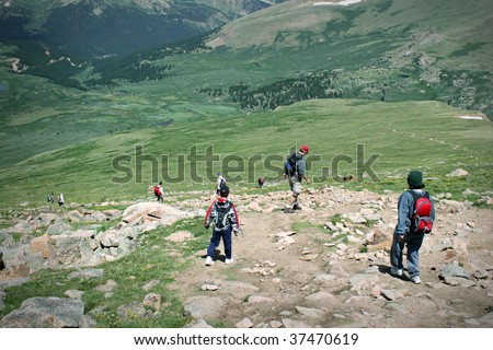 Mountain Summit Hikers Summer. Colorado Summer Mountain Backcountry Scene. Great for themes of nature, summer, mountains, outdoor recreation, travel destinations, background scenic. - stock photo
