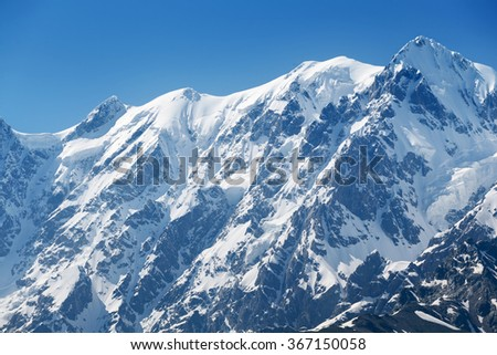 Mountain summit under snow. Winter landscape in cold sunny day. Blue sky above a peak