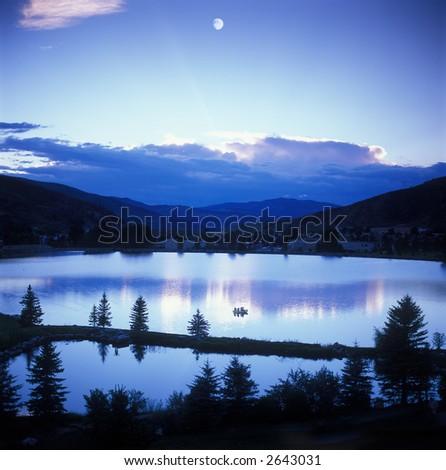 Mountain sunset/moonset over lake - stock photo