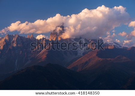 Mountain top in clouds. Beautiful sunset. Mount Ushba. Caucasus, Georgia, Zemo Svaneti - stock photo