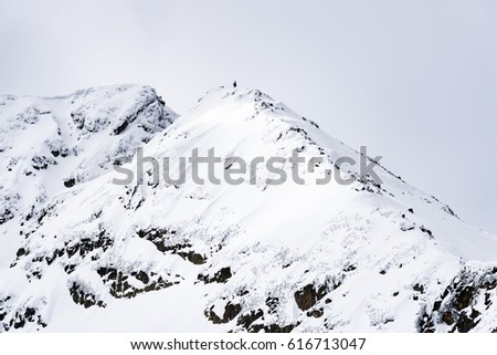 Mountain top in snow against a cloudy sky in winter