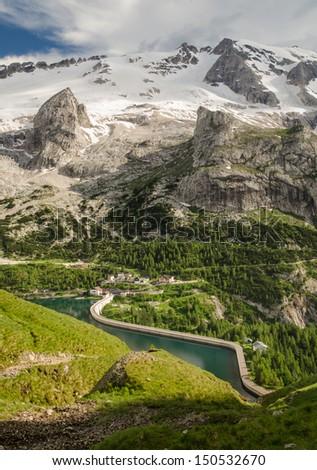 Mountain Tops and Meadows in Summer, Dam on Lake Fedaia, Marmolada, Dolomites, Alps, Italy - stock photo