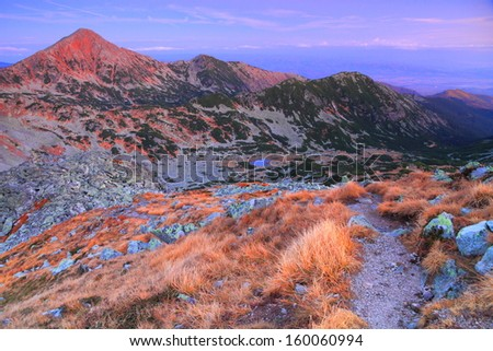 Mountain trail and distant peaks before dawn - stock photo