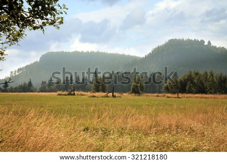 Mountain trail on meadow in Pasterka and view on Szczeliniec Wielki i Szczeliniec May, Polish village in Table Mountais. Early morning. - stock photo