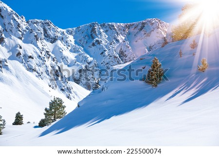 Mountain valley and snow on sunny day with high peaks on background - stock photo