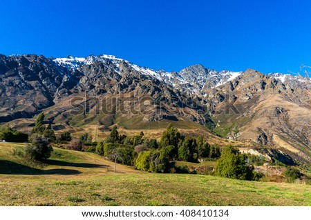 Mountain valley view. Nature landscape background photo of snow covered mountains and green grass, Otago, New Zealand. Beautiful  mountain valley winter landscape - stock photo