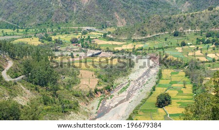 mountain valley with dry stream and cultivated farms In Indian Himalaya