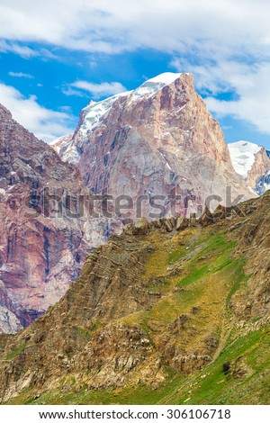 Mountain vertical scene. Bright landscape of Fan Mountains in Tajikistan with mixed layer of colors green meadow on foreground brown rocks in middle red peaks with glaciers and snow on background - stock photo