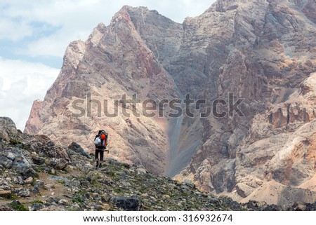 Mountain View and Hiker. Person with Backpacks Walking Up on Rocky Trail along Green Meadow and High Rock Walls and Summits on Background Blue Sky Clouds Sunny - stock photo