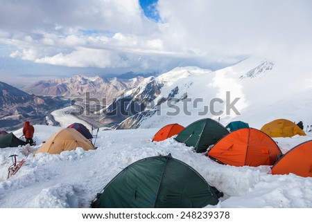 Mountain view from  Lenin peak camp 4. Climbers preparing for  summit attempt in their tents. Pamir mountains, Kyrgyzstan
