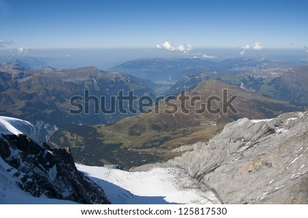 Mountain view of valley below, snow in foreground and town in distance - stock photo