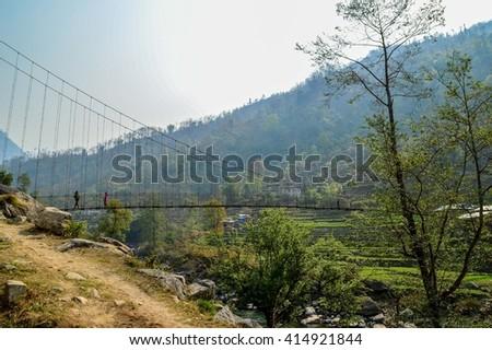 Mountain view with suspension bridge, Himalayan mountains, Nepal - stock photo