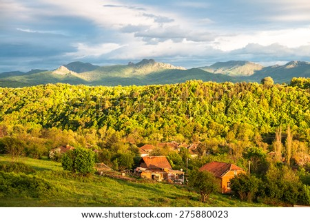 Mountain village at sunset in spring with the Balkan mountain range in the back