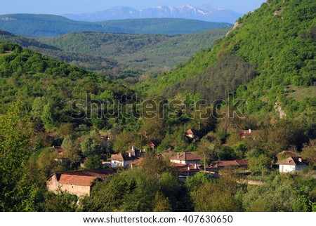 Mountain village in the spring and snowy mountain ridge in the background in Veliko Tarnovo province in Bulgaria - stock photo