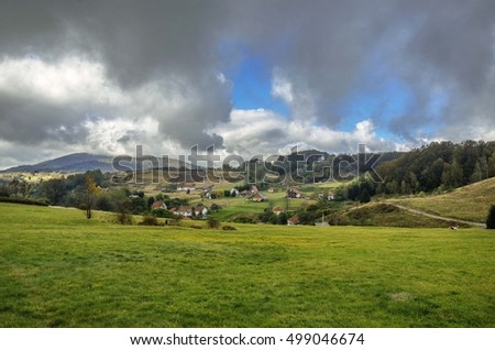 Mountain village landscape with green field of grass and dark blue clouds