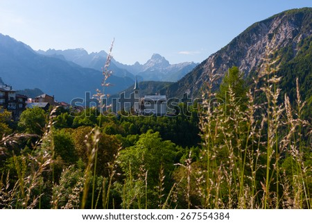 mountain village with the church at the Alps  - stock photo