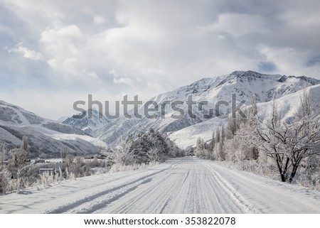 Mountain winter landscape, an icy road leading towards Ala-Archa national park, Kyrgyzstan.  - stock photo