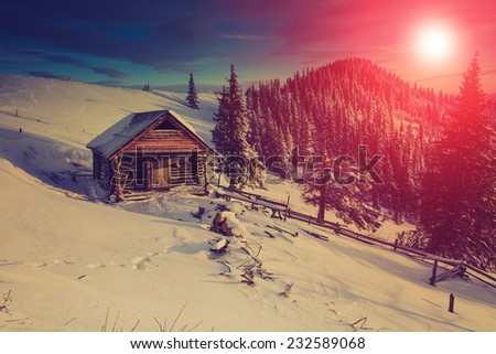 Mountain winter landscape.View of the  old farm. Fantastic evening glowing by sunlight.Retro filter.  - stock photo