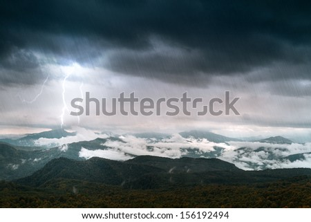 mountain with sky and lighting under rain - stock photo
