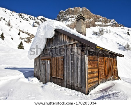 Mountain wooden cabin log in the Dolomites, Passo Fedaia, Italy - stock photo