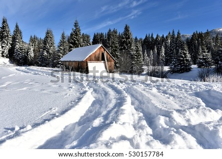Mountain wooden chalet covered with fresh snow at winter