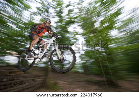 Mountainbike downhill in forrest - blurred motion - stock photo
