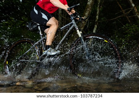 mountainbiker driving through a creek - stock photo