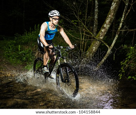 mountainbiker driving through astreambed - stock photo