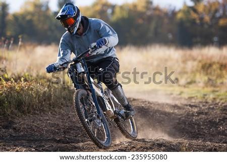Mountainbiker rides in autumn path - stock photo