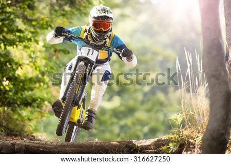 Mountainbiker rides in forest - stock photo