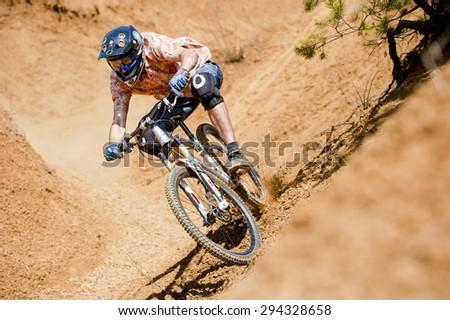 Mountainbiker rides in gorge on desert - stock photo