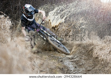 Mountainbiker rides on path in mud - stock photo