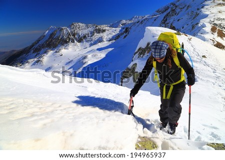 Mountaineer ascending a snowy ridge in sunny day