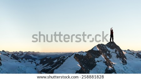 Mountaineer at peak of mountain enjoying natural landscape - stock photo