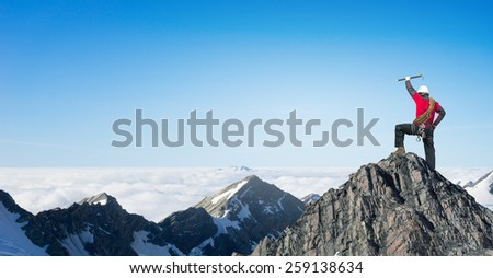 Mountaineer at peak of mountain enjoying natural landscape - stock photo