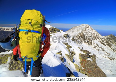 Mountaineer carries a yellow backpack field on the mountain in sunny day - stock photo