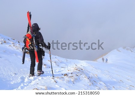 Mountaineer carries skies and gear attached to the backpack - stock photo